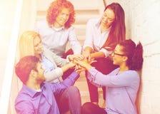 Gruppo con le mani sopra a vicenda sulla scala Fotografia Stock