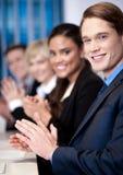 Gruppo corporativo che si siede in una fila e che applaude Fotografie Stock Libere da Diritti