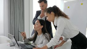 Gruppo creativo che lavora al computer portatile nello spazio ufficio, confrontare le idee della gente dell'ufficio sul computer video d archivio
