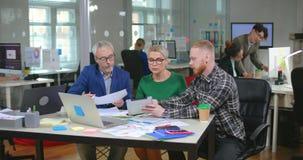 Gruppo creativo che progetta nuova etichetta facendo uso del computer portatile e della compressa video d archivio