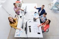 Gruppo creativo con i computer che mostrano i pollici su Fotografia Stock