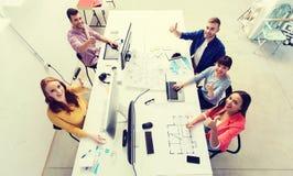 Gruppo creativo con i computer che mostrano i pollici su Fotografie Stock