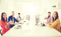 Gruppo creativo con i computer che mostrano i pollici su Immagini Stock