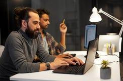 Gruppo creativo con il computer che funziona tardi all'ufficio fotografie stock