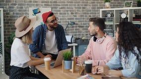Gruppo creativo dei progettisti che parlano nell'ufficio intorno al 'brainstorming' della tavola sul lavoro stock footage