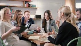 Gruppo creativo di affari alla tavola in un ufficio startup moderno Il capo femminile spiega i dettagli del progetto fotografie stock libere da diritti