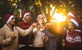 Gruppo degli amici con i cappelli di Santa che celebra il Natale con champagne e le stelle filante all'aperto immagini stock