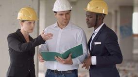Gruppo degli architetti che paragonano programma di costruzione di alloggi alla costruzione Fotografia Stock Libera da Diritti