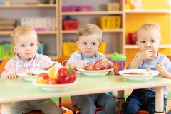 Gruppo dei bambini che mangia le verdure nella stanza dinning di asilo fotografia stock