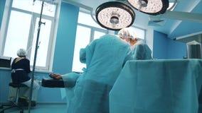 Gruppo dei chirurghi professionisti che eseguono intervento di alta chirurgia su un paziente nella sala operatoria dell'ospedale  video d archivio