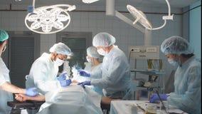 Gruppo dei chirurghi professionisti che lavorano all'ospedale che esegue procedura chirurgica stock footage
