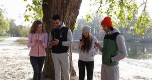 Gruppo dei giovani facendo uso di alba all'aperto dello Smart Phone, mattina Autumn Park Near Tree di comunicazione della rete di stock footage