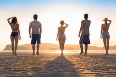 Gruppo dei giovani sulla spiaggia alle vacanze estive di tramonto, retrovisione posteriore di camminata della spiaggia degli amic Fotografie Stock