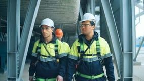 Gruppo dei lavoratori che camminano sull'impianto industriale stock footage