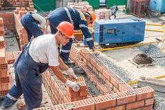 Gruppo dei muratori sulla costruzione della casa Fotografie Stock Libere da Diritti
