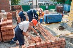 Gruppo dei muratori sulla costruzione della casa Immagini Stock Libere da Diritti
