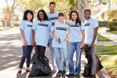 Gruppo dei volontari che prendono lettiera in via suburbana Fotografia Stock