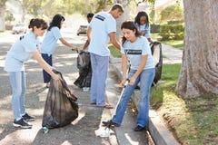 Gruppo dei volontari che prendono lettiera in via suburbana Immagine Stock