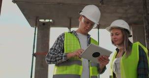 Gruppo del cantiere o architetto e costruttore o lavoratore con i caschi discutere su un piano della costruzione dell'impalcatura stock footage