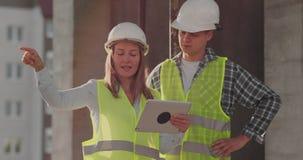 Gruppo del cantiere o architetto e costruttore o lavoratore con i caschi discutere su un piano della costruzione dell'impalcatura archivi video
