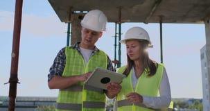 Gruppo del cantiere o architetto e costruttore o lavoratore con i caschi discutere su un piano della costruzione dell'impalcatura video d archivio