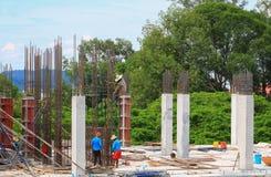 Gruppo del lavoratore della costruzione che lavora all'alloggio della costruzione del terreno alto nel posto di lavoro del sito Immagini Stock