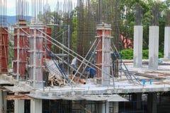 Gruppo del lavoratore della costruzione che lavora all'alloggio della costruzione del terreno alto nel posto di lavoro del sito Immagine Stock