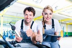 Gruppo del meccanico che lavora nell'officina dell'automobile fotografia stock