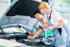 Gruppo del meccanico che lavora nell'officina dell'automobile immagini stock