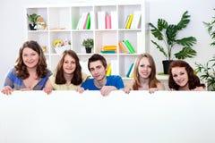 Gruppo dell'adolescente che tiene grande documento vuoto Immagini Stock Libere da Diritti