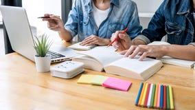 Gruppo dell'istitutore o dello studente di college della High School che si siede allo scrittorio in biblioteca che studia e che  immagini stock libere da diritti