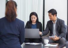 Gruppo della gente di affari tre che lavora insieme su un computer portatile Fotografia Stock