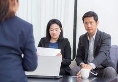 Gruppo della gente di affari tre che lavora insieme su un computer portatile con nel corso di una riunione che si siede intorno a Immagini Stock Libere da Diritti