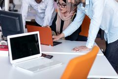 Gruppo della giovane impresa sulla riunione in 'brainstorming' interno dell'ufficio luminoso moderno, funzionamento sul computer  fotografie stock