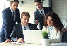Gruppo della giovane impresa sulla riunione nell'ufficio luminoso moderno interno e sul funzionamento sul computer portatile Immagine Stock