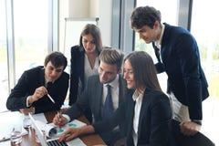 Gruppo della giovane impresa sulla riunione nell'ufficio luminoso moderno interno e sul funzionamento sul computer portatile Fotografia Stock