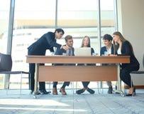 Gruppo della giovane impresa sulla riunione nell'ufficio luminoso moderno interno e sul funzionamento sul computer portatile Fotografia Stock Libera da Diritti