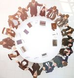 Gruppo della grande impresa che si siede alla tavola rotonda e che solleva la sua h Fotografia Stock