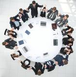 Gruppo della grande impresa che si siede alla tavola rotonda e che solleva le sue mani su Fotografie Stock Libere da Diritti
