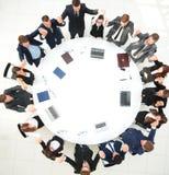 Gruppo della grande impresa che si siede alla tavola rotonda e che solleva le sue mani su Immagine Stock Libera da Diritti