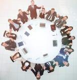 Gruppo della grande impresa che si siede alla tavola rotonda e che solleva le sue mani su Immagini Stock Libere da Diritti