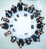 Gruppo della grande impresa che si siede alla tavola rotonda e che solleva le sue mani su Fotografia Stock Libera da Diritti