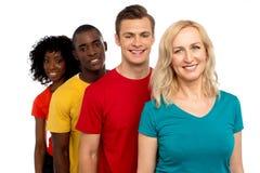 Gruppo di adolescenti allegri che si levano in piedi in una riga Fotografia Stock