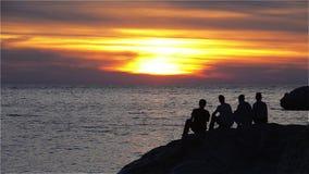 Gruppo di adolescenti che guardano il tramonto sulla riva di mare video d archivio