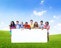 Gruppo di adolescenti che posano con un bordo bianco fotografia stock libera da diritti