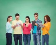 Gruppo di adolescenti con gli smartphones ed il pc della compressa Fotografie Stock Libere da Diritti