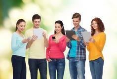 Gruppo di adolescenti con gli smartphones ed il pc della compressa Immagine Stock Libera da Diritti