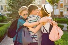 Gruppo di adolescenti felici 13, 14 anni camminante lungo la via della città, abbraccio degli amici Fotografia Stock Libera da Diritti