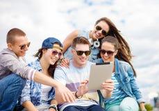 Gruppo di adolescenti sorridenti che esaminano il pc della compressa fotografia stock