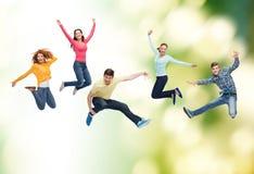 Gruppo di adolescenti sorridenti che saltano in aria Fotografia Stock